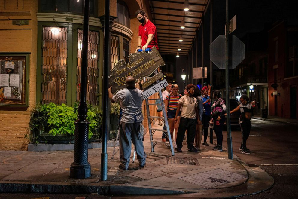 Người dân New Orleans gỡ bảng hiệu nhà hàng trước khi bão Zeta đổ bộ vào thành phố - Ảnh: Reuters