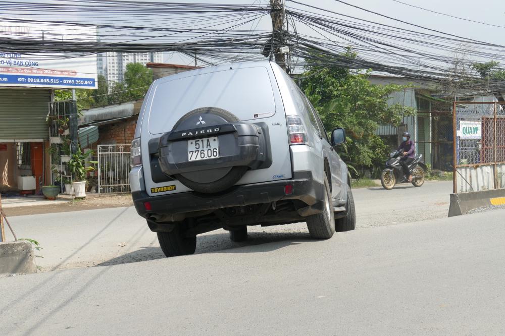 Một chiếc xe hơi di chuyển với tốc độ chậm khi lưu thông trên đoạn đường đau khổ