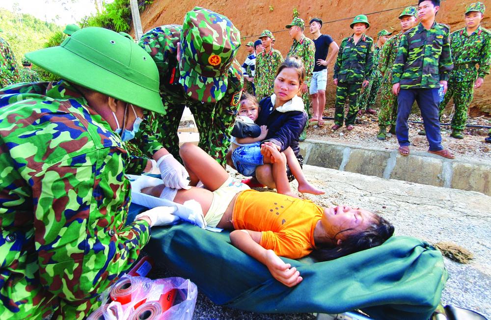 Các chiến sĩ quân y đang sơ cứu cho bé Hồ Hà My (một trong hai con gái của chị Hà may mắn thoát chết) ẢNH: NGUYỄN DƯƠNG