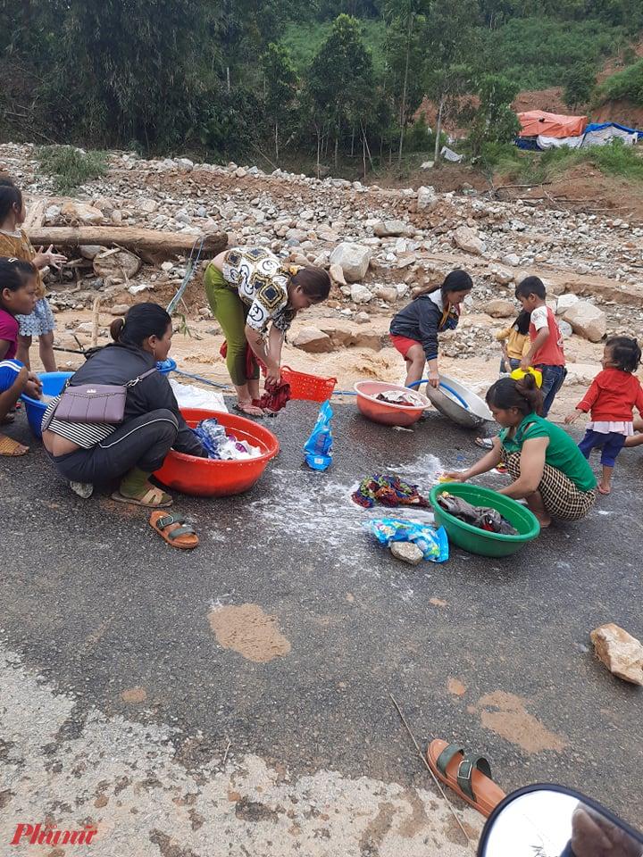 Hàng trăm người đang lâm vào cảnh màn trời chiếu đất. Họ tranh thủ giặt giũ áo quần bên dòng nước lũ đục ngầu