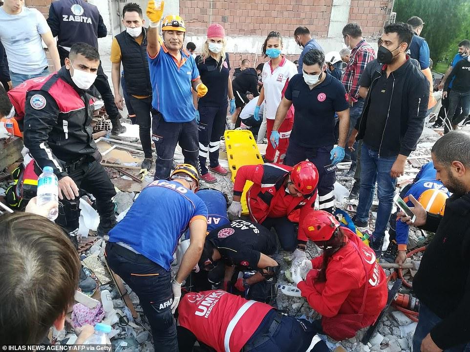 Những người bị thương được cắt ra khỏi đống đổ nát của một tòa nhà lật đổ ở Izmir, Thổ Nhĩ Kỳ, sau khi trận động đất xảy ra