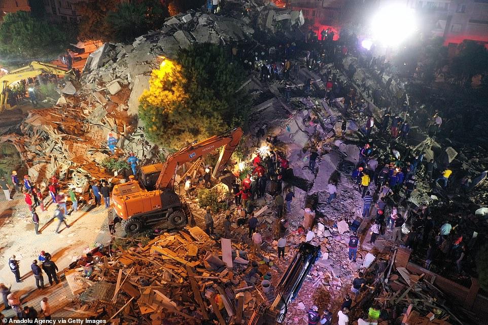 Máy móc nâng hạng nặng được sử dụng để sàng lọc đống đổ nát của một tòa nhà bị sập ở Izimir, Thổ Nhĩ Kỳ, sau khi nó bị động đất