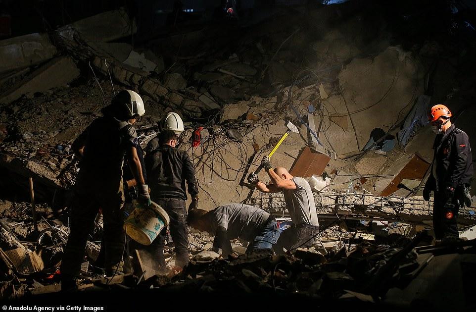 Nhân viên cứu hộ cố gắng dọn dẹp các mảnh vỡ của một tòa nhà bị sập trong khi tìm kiếm những người sống sót