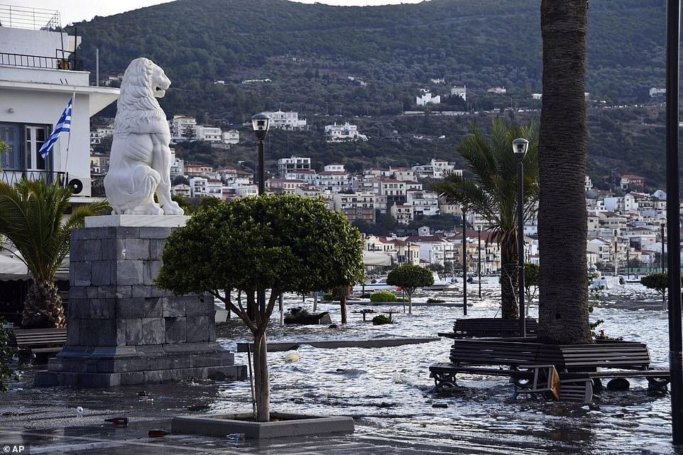 Một bức tượng sư tử nhìn ra quảng trường ngập nước với những chiếc ghế dài và cây cối bao quanh bởi nước ở cảng Vathi của Hy Lạp