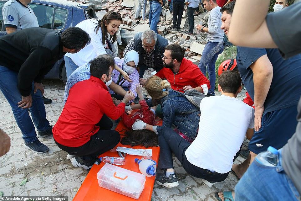 Mọi người vây quanh móng của một chiếc máy xúc khi họ tìm kiếm những người sống sót tại một tòa nhà bị sập ở Izmir ngày nay
