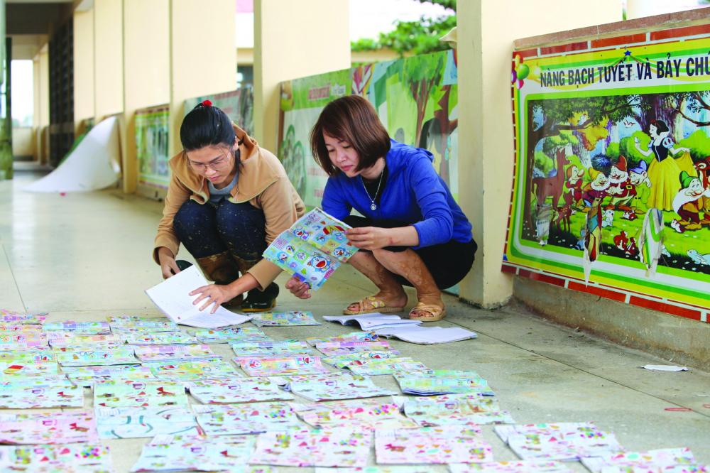 Giáo viên Trường tiểu học Hàm Ninh phơi số tập, sách còn sót lại sau lũ - Ảnh: Thuận Hóa