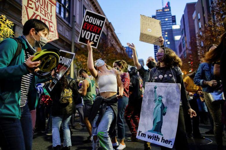 """Ngoài ăn mừng, một số đám động cũng giương cao khẩu hiệu """"kiểm đếm từng phiếu bầu"""" để chắc chắn các cơ quan kiểm phiếu không loại bỏ phiếu bầu vì áp lực pháp lý của Tổng thống Donald Trump."""