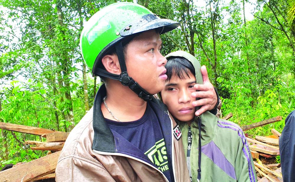 Cậu bé Lê Thanh Tú ( phải) dựa vào thầy giáo khi vẫn chưa hết kinh hoàng nỗi mất cha - Ảnh: Việt Dũng