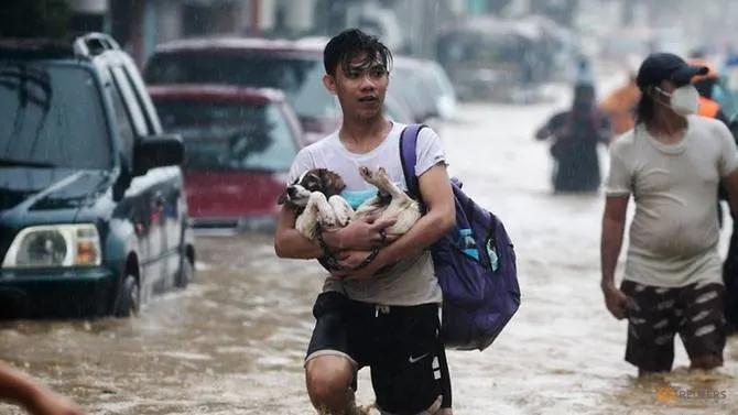 Người dân mang theo đồ đạc băng qua một con phố ngập lụt để đến nơi trú ẩn ở thành phố Marikini, ngoại ô Manila, hôm 12/11 - Ảnh: AFP