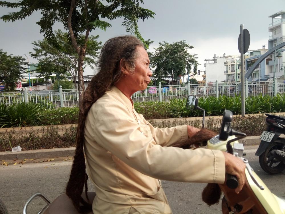 Ông Tư vắt đuôi tóc vào tay trái khi chạy xe.