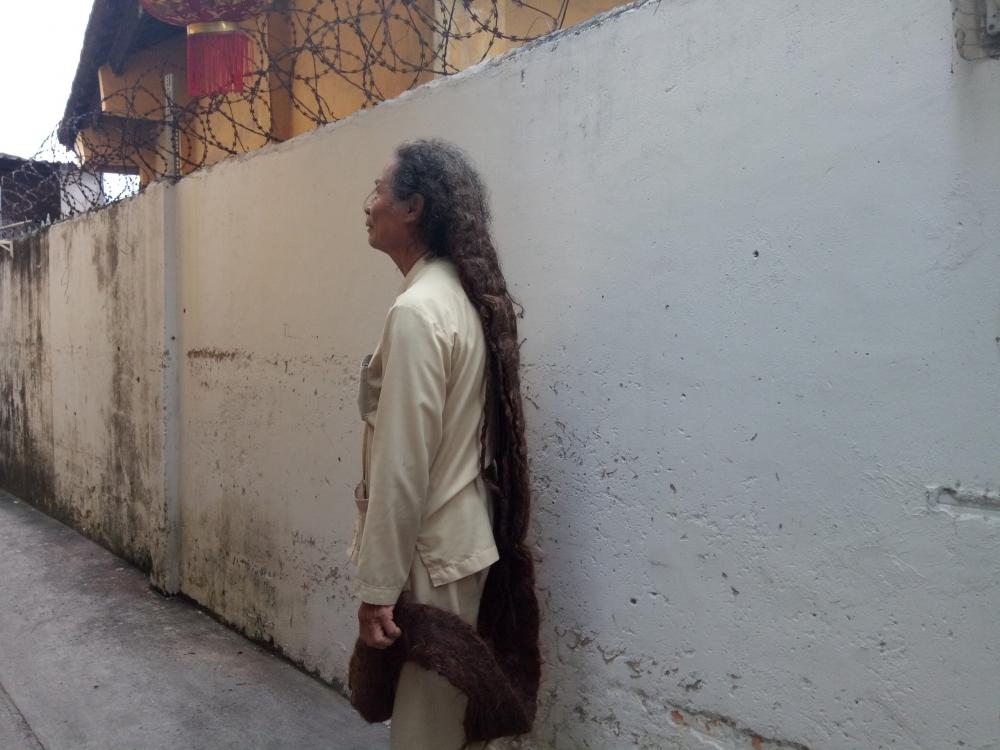 Lúc đi lại ông Tư luôn phải cầm phần đuôi tóc lêm.