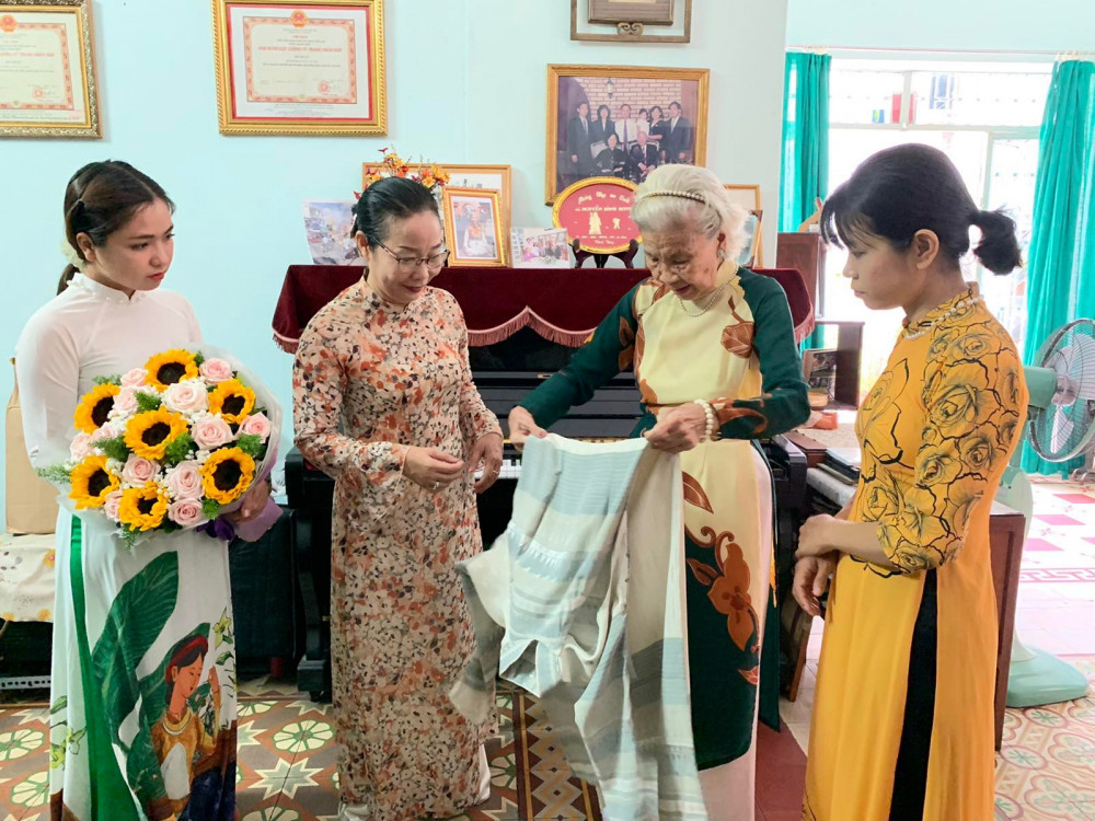 Nhà giáo Nguyễn Bình Minh (thứ hai từ phải sang) trao áo dài cho bà Nguyễn Thị Ngọc Vân