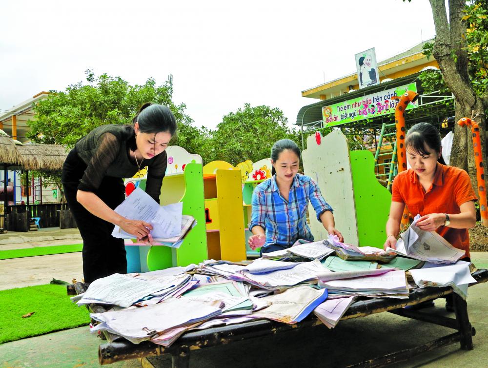 Đến trưa 19/11, cá c cô giáo Trường mầm non Phong Bình 2 vẫn tiếp tục phơi tập, sách do bị ngâm nước lũ dài ngày ẢNH: THUẬN HÓA