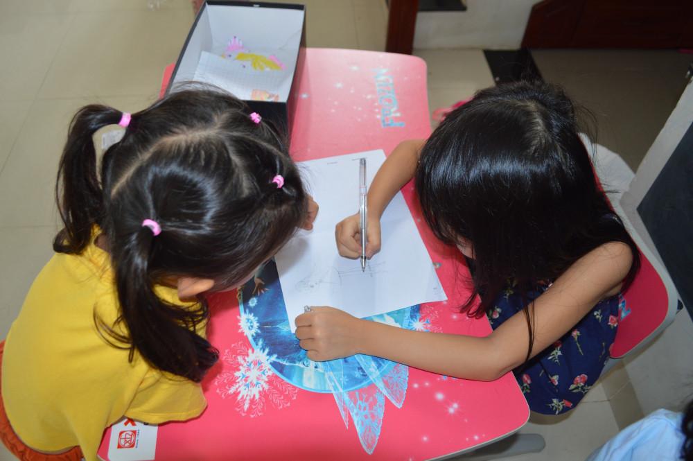 Hai học sinh trường tiểu học ở Quảng Ngãi đang vẻ cô giáo của mình