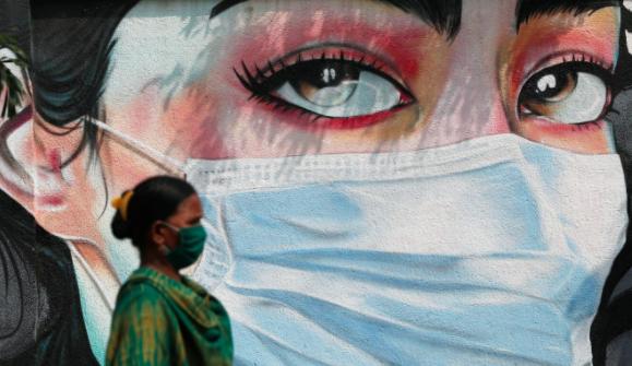 Một người phụ nữ đeo khẩu trang đi ngang qua bức vẽ graffiti của một người phụ nữ đeo mặt nạ ở Mumbai. Ảnh: Reuters