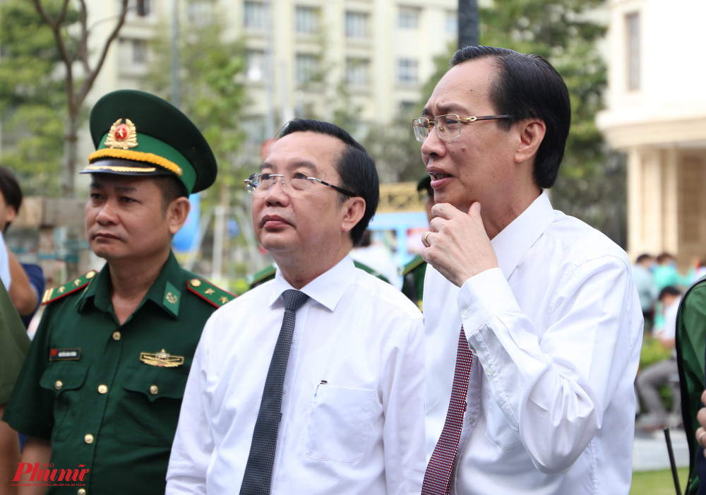Ông Lê Thanh Liêm, ông Trần Thế Thuận (giữa) theo dõi những bức ảnh ở triển lãm
