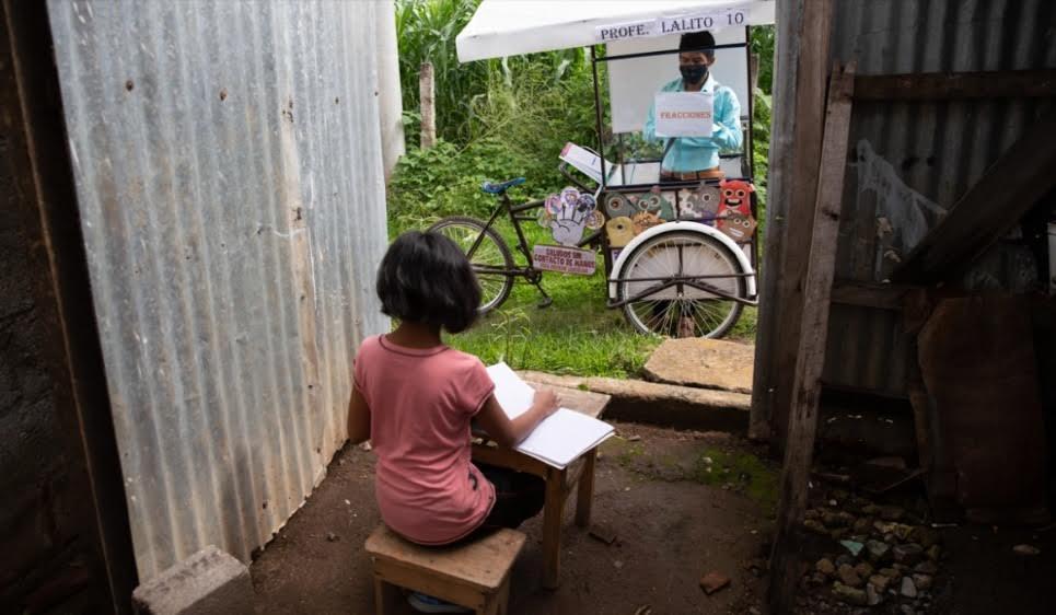 """: Giáo viên người Guatemala - Gerardo Ixcoy, đạp chiếc xe ba gác """"lớp học"""" tự chế đến nhà các học sinh lớp sáu của mình trong bối cảnh đại dịch COVID-19. (Ảnh: AP)"""