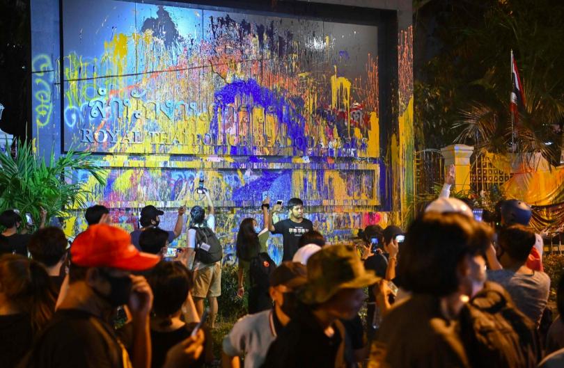Những người biểu tình ủng hộ dân chủ chụp ảnh bên cạnh tấm biển đổ sơn cho trụ sở cảnh sát trong một cuộc biểu tình chống chính phủ ở Bangkok. Ảnh: AFP