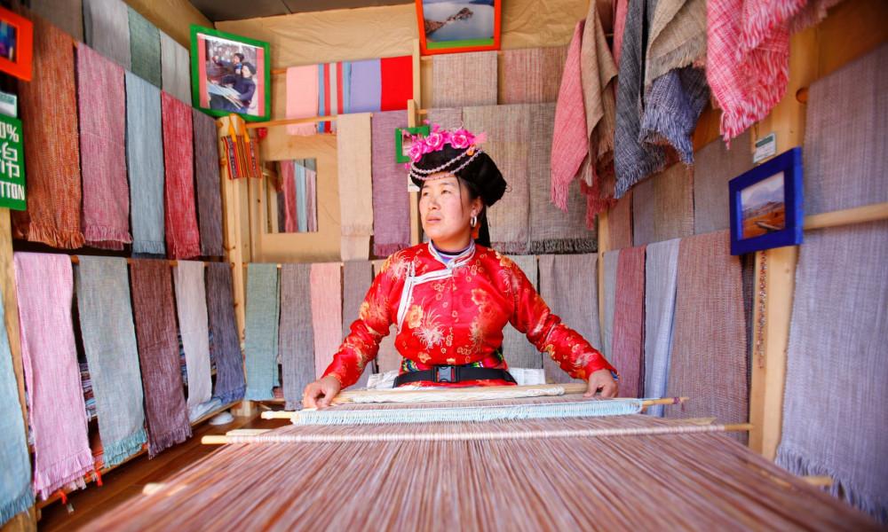 Một phụ nữ người đang dệt vãi bên trong cửa hiệu của mình - Ảnh: Chien-min Chung/Getty Images