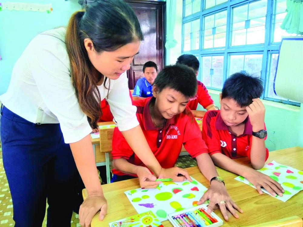 Cô giáo Tường Văn chỉ bài cho học trò bị khuyết tật nghe nói Huỳnh Văn Sỹ