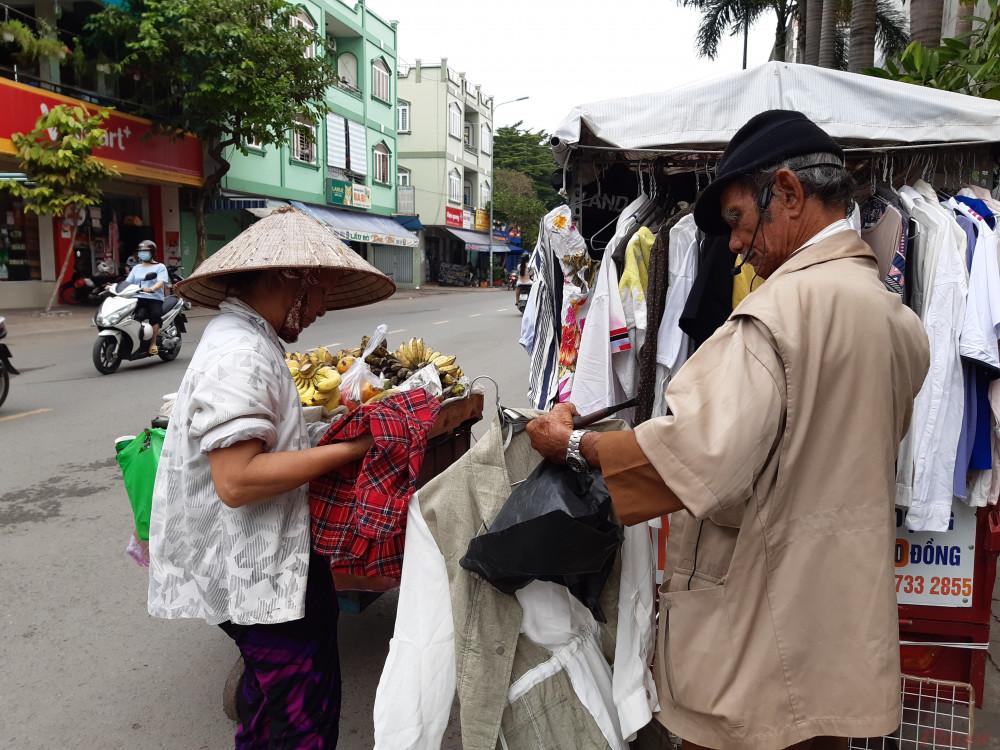 Người phụ nữ bán hàng rong hồ hởi chọn cho mình một chiếc áo phù hợp