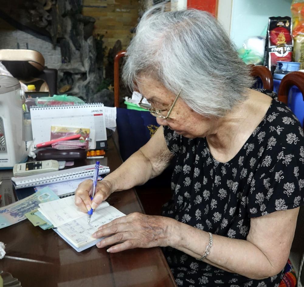 Cụ Mỹ tuổi ngoài chín mươi vẫn phụ giúp nhóm ghi sổ sách các khoản thu, chi