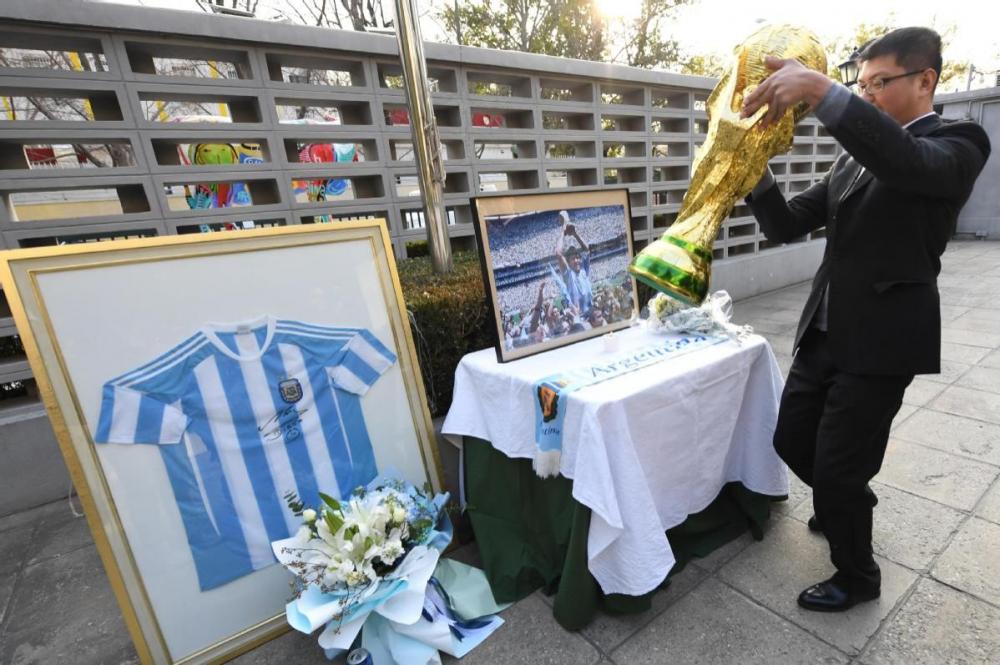 Một nhân viên của đại sứ quán Argentina ở Trung Quốc đặt bàn tưởng niệm huyền thoại bóng đá Diego Maradona tại đại sứ quán ở Bắc Kinh.