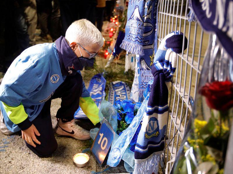 Một người hâm mộ quỳ xuống đặt hoa để thương tiếc cái chết của huyền thoại bóng đá Argentina Diego Maradona bên ngoài sân vận động San Paolo ở Naples, Ý.
