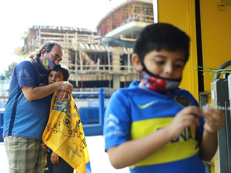 Người cha và hai cậu con trai đến bày tỏ lòng tiếc thương Diego Armando Maradona, bên ngoài sân vận động Alberto J. Armando 'La Bombonera', ở Buenos Aires.