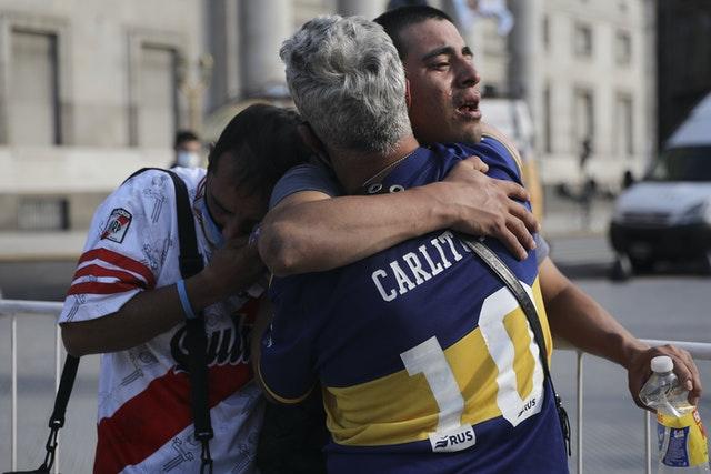 Cổ động viên của hai đội đối thủ Boca Juniors (phải) và River Plate (trái), ôm hôn nhau để cùng chia sẻ nỗi buồn.