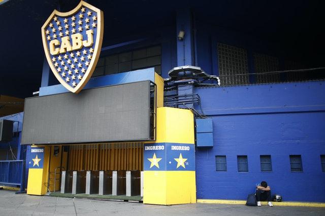 Một người hâm mộ bóng đá ngồi lặng lẽ bên ngoài La Bombomera, sân nhà của Boca Juniors, một câu lạc bộ cũ của Maradona.