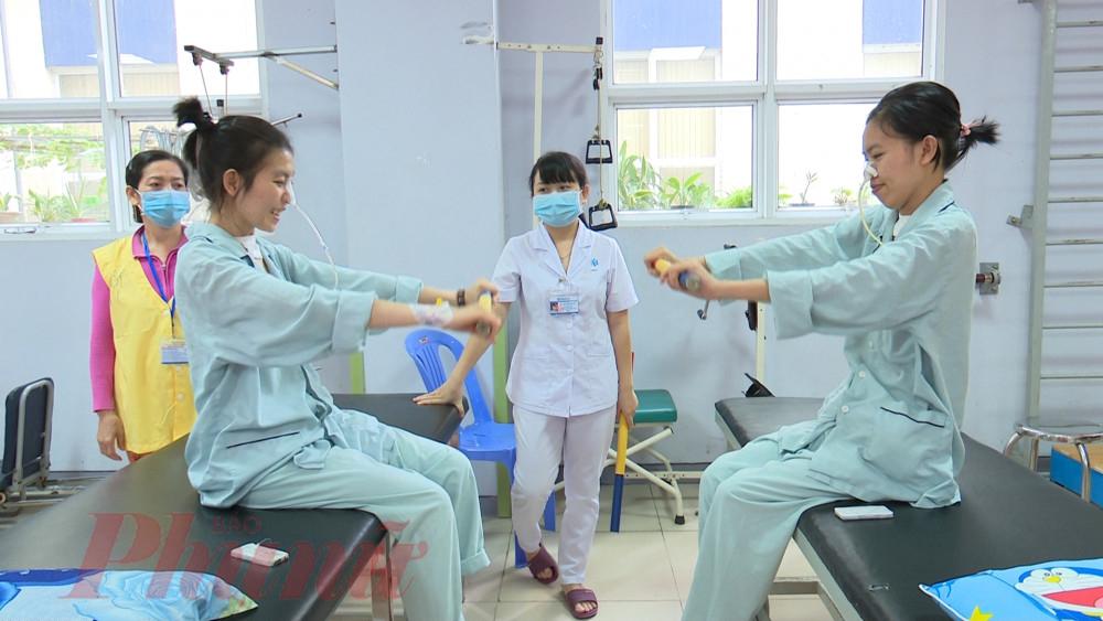 Bệnh nhân Gẫm (bên phải) dù được xuất viện vẫn phải tập vật lý trị liệu
