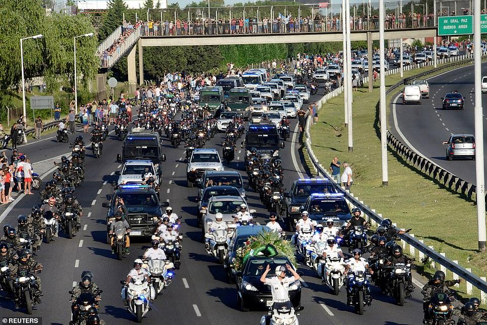 Người dân đứng trên cầu và xung quanh đường ngắm nhìn đội an ninh hộ tống xe tang chở Maradona đi an táng trên đường cao tốc 25 de Mayo.
