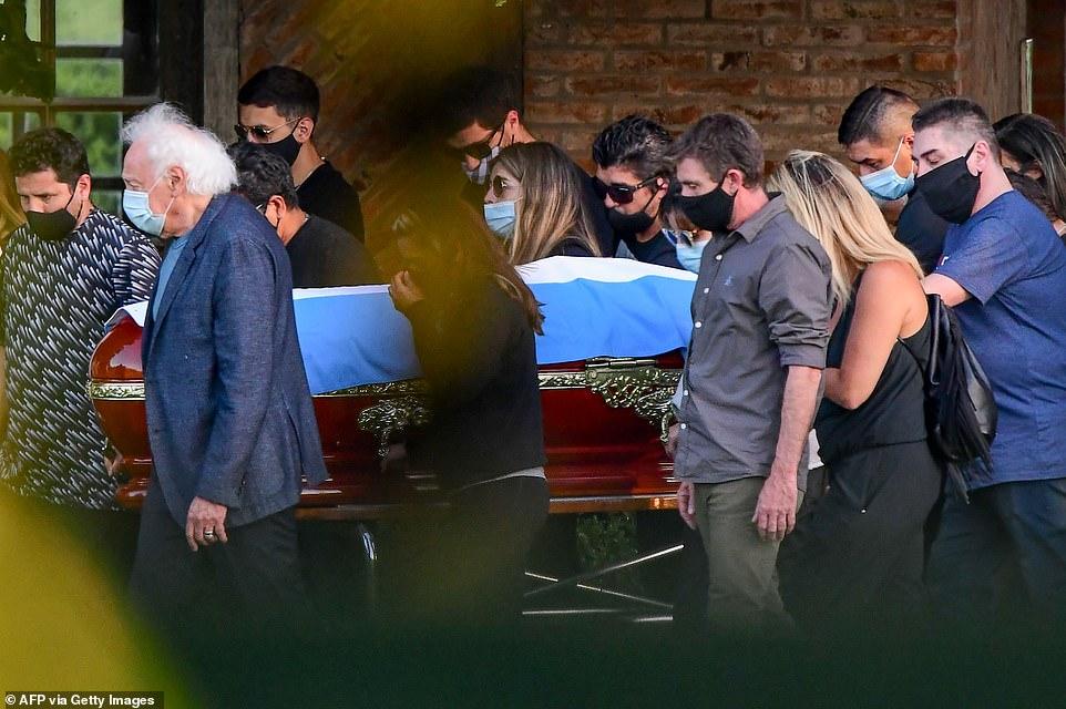 """Một nhóm nhỏ gia đình và bạn bè khiêng quan tài của """"Cậu bé vàng"""" cùng quốc kỳ Argentina. Khoảng một chục người thân tập trung để làm lễ và chôn cất huyền thoại."""