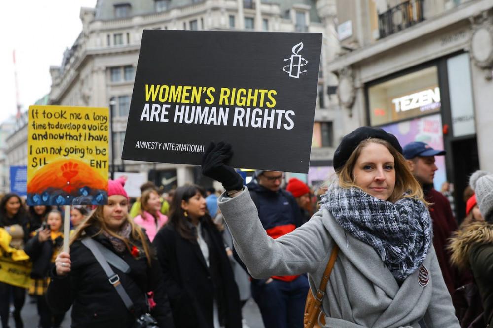 """Một người tham dự với tấm biển """"Quyền phụ nữ chính là nhân quyền"""" trong sự kiện diễu hành vì quyền phụ nữ tháng 1.2019 tại London, Anh. (Ảnh: Insider)"""