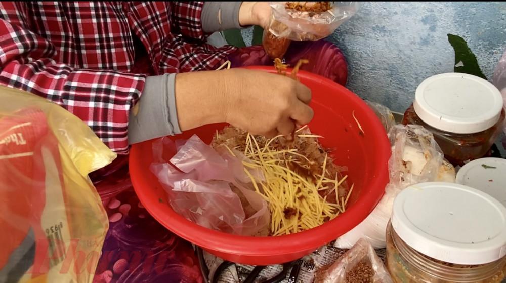 Người bán bánh tráng trộn tay không bốc nguyên liệu, bào xoài, cắt rau răm,... rồi vô tư cầm, nắm tiền cho khách. Ảnh: Quốc Thái