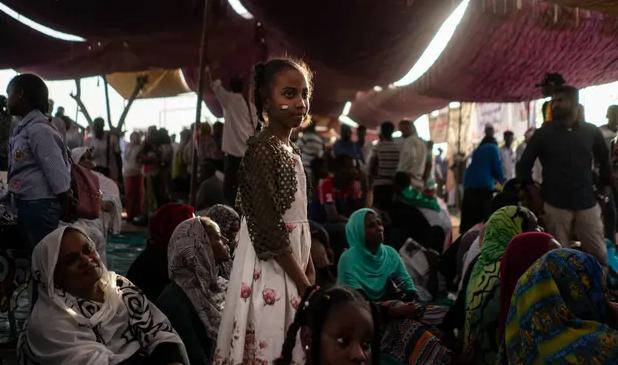 Một cô gái Sudan đứng nhìn những người biểu tình yêu cầu thay đổi sau khi Omar al-Bashir bị lật đổ vào năm ngoái. Ảnh: Getty Images