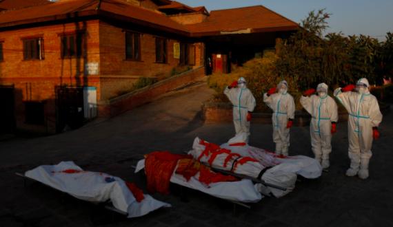 Các nữ binh sĩ mặc trang bị bảo hộ cá nhân tưởng nhớ thi thể nạn nhân coronavirus tại một lò hỏa táng ở Nepal. Ảnh: Reuters