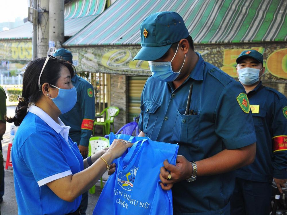 Bà Lương Thanh Trúc- Chủ tịch Hội LHPN Q.6 (trài) trao tặng quà cho chiến sĩ tuyến đầu chống dịch