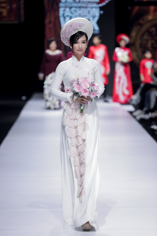MC Quỳnh Chi ngọt ngào với thiết kế màu trắng phối họa tiết màu hồng phù hợp với cô dâu chuộng vẻ ngoài nữ tính.