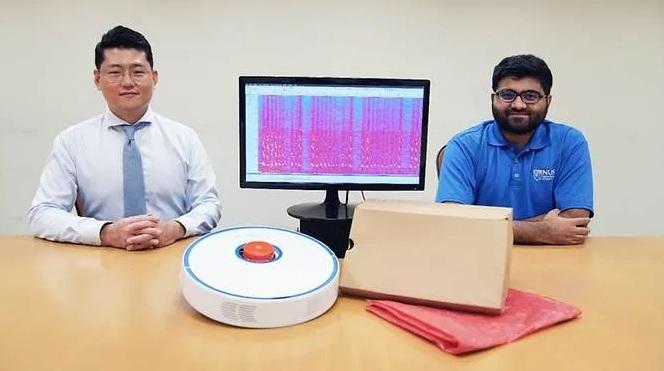 Trợ lý giáo sư Jun Han (trái) và nghiên cứu sinh tiến sĩ Sriram Sami từ NUS Computing với robot hút bụi, màn hình hiển thị sóng âm đã thu hồi và các vật dụng gia đình thông thường được làm từ vật liệu có thể phản xạ âm thanh.