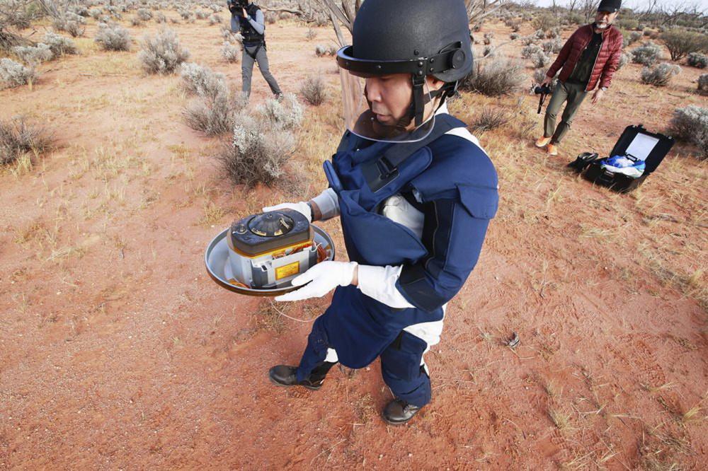 Nhân viên Cơ quan Thám hiểm hàng không vũ trụ Nhật Bản (JAXA) thu hồi viên nang do tàu Hayabusa2 gửi về và đã hạ cánh tại Woomera, miền Nam nước Úc - Ảnh: AP