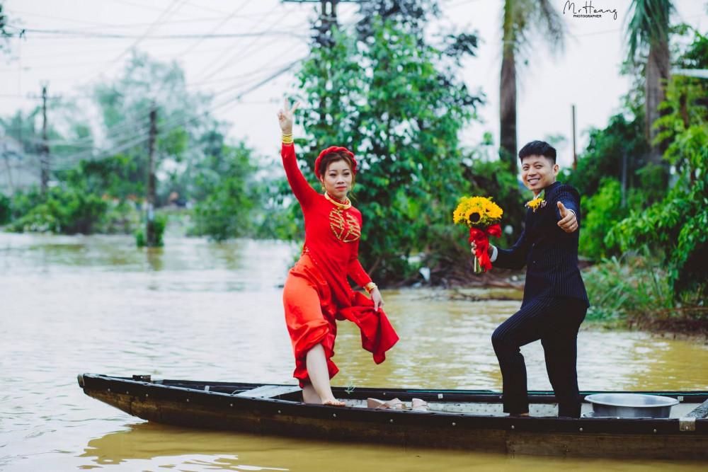 Cô dâu Lê Nhi và chú rể là Tôn Đức ( xã Quảng Phú, huyện Quảng Điền, tỉnh Thừa Thiên Huế) đi chân đất, vén ống quần cười tươi trong đám cưới giữa mùa bão lụt.