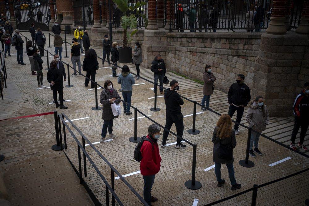 Mọi người chờ đợi đến lượt mình để được gọi xét nghiệm PCR cho COVID-19 bên ngoài một bệnh viện ở Barcelona, Tây Ban Nha. (Ảnh AP / Emilio Morenatti, Tệp)