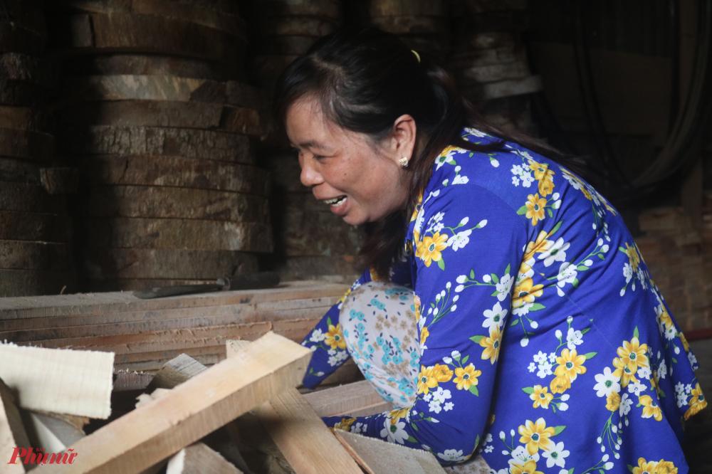 Sau khi cưa gỗ, chị Muội dọn dẹp đống gỗ vụn để tận dụng làm những đồ vật khác.