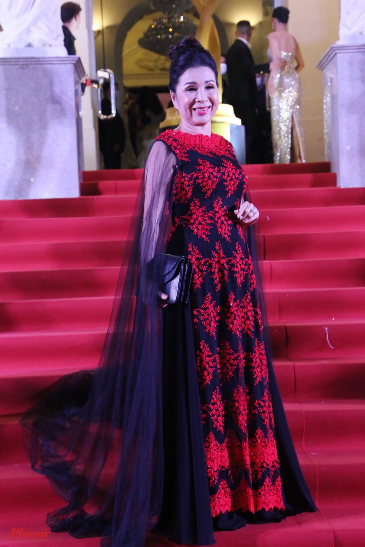 NSND Kim Xuân diện áo dài cách điệu với tà dài phía sau. Hoạ tiết màu đỏ được đính nổi bật lên trên nền sắc đen. Nữ nghệ sĩ cho biết bà cảm thấy thú vị khi diện thiết kế này.