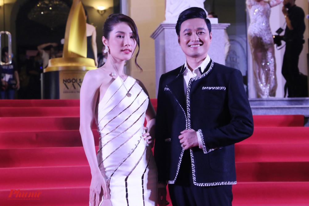 Diễm My 9X sánh vai củng ca sĩ Quang Vinh trên thảm đỏ. Nữ diễn viên diện váy màu trắng với những khoảng hở độc đáo nhờ ráp nối nhiều mảnh vải đơn lẻ với nhau.