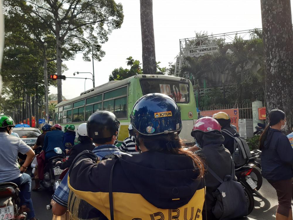 Xe buýt chiếm hết phần đường của xe máy đi thẳng và rẽ phải. Xe máy liền tràn sang phần đường khác để chờ đèn đỏ, những xe rẽ phải thì bóp kèn inh ỏi. - Ảnh: Lâm Ngọc