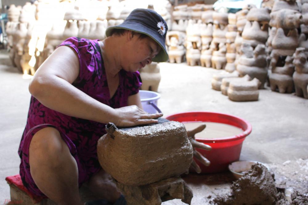 Chị Linh đã 50 tuổi và theo nghề được hơn 10 năm. Chị đang đắp đất cho khuôn để chuẩn bị nung và chế đồng.ng