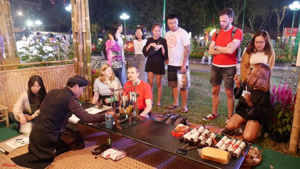 Du khách và người dân cùng ngắm nhìn hình ảnh ông đồ cho chữ đầu năm tại lễ hội Tết Việt 2020. Ảnh: Thiên Ân